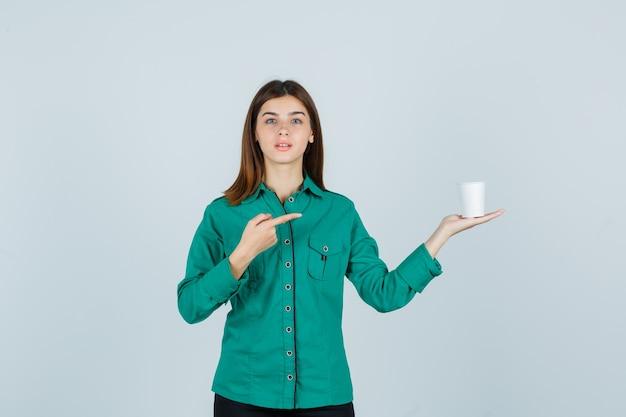Jovem senhora em uma camisa segurando um copo plástico de café enquanto aponta para o lado direito e olhando a vista frontal focada.
