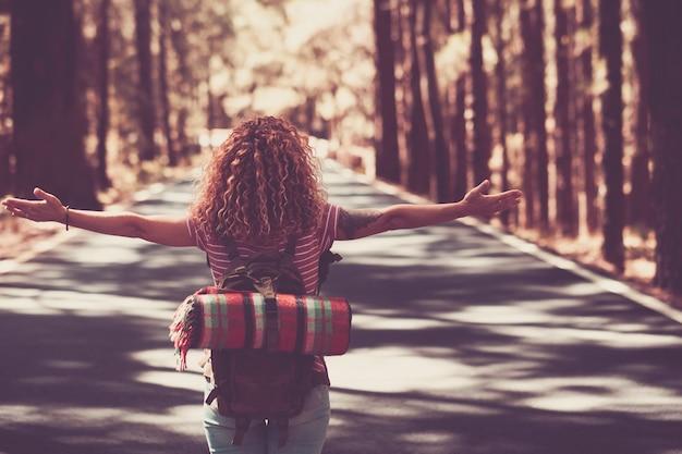 Jovem senhora encaracolada caminhando no meio de uma estrada de longo caminho com a floresta ao redor. imagem do conceito de liberdade e independência para pessoas com sede de viagens que amam viajar e aproveitar o mundo e as distâncias