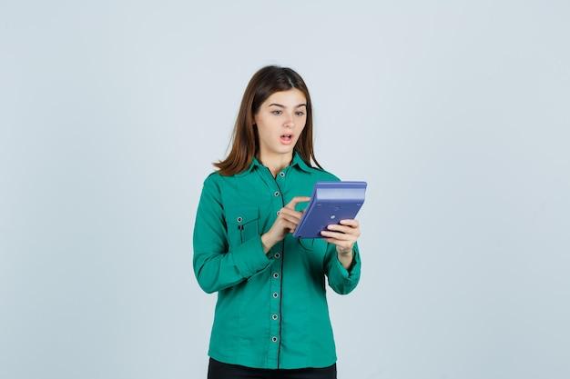 Jovem senhora fazendo cálculos na calculadora na camisa verde e parecendo maravilhada. vista frontal.