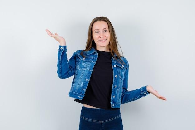 Jovem senhora fazendo escalas gesto na blusa, jaqueta e olhando confiante, vista frontal.