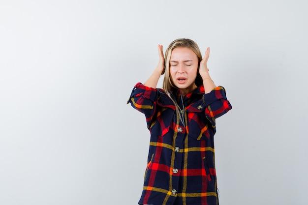 Jovem senhora fechando as orelhas com as mãos na camisa e parecendo irritada, vista frontal.