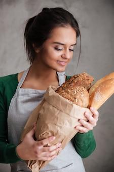 Jovem senhora feliz padeiro em pé e segurando o pão.