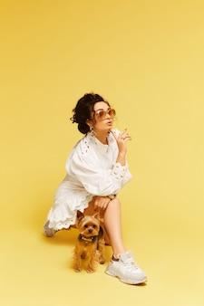 Jovem senhora glamourosa em óculos de sol da moda e vestido branco, posando com bolsa de ouro e te ...