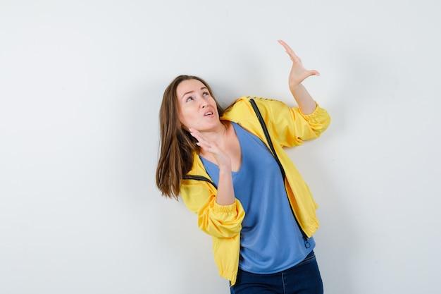 Jovem senhora levantando as mãos para se defender em t-shirt, jaqueta e parecendo assustada, vista frontal.