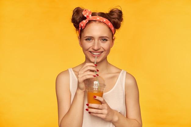 Jovem senhora, linda mulher ruiva com dois pãezinhos e faixa de cabelo parecendo feliz. vestindo camisa branca e segurando seu smoothie saudável. sorrindo assistindo isolado na parede amarela