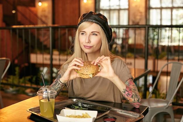 Jovem senhora loira de cabelos compridos satisfeita com tatuagens posando sobre o interior de um café moderno e segurando um hambúrguer nas mãos, olhando para o lado e sorrindo feliz, usando roupas da moda