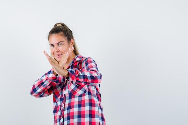 Jovem senhora mostrando gesto de golpe de caratê em camisa xadrez e parecendo confiante. vista frontal.