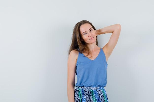 Jovem senhora posando com a mão atrás da cabeça em camiseta, saia e bonita, vista frontal.