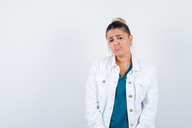 Jovem senhora posando com camisa, jaqueta branca e parecendo decepcionada, vista frontal.