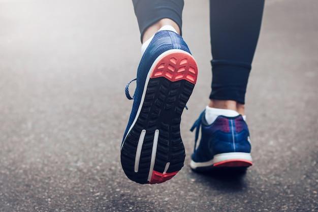 Jovem senhora que corre em uma estrada rural durante o por do sol nas sapatilhas azuis com sola preta.