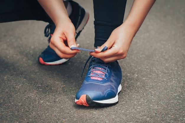 Jovem senhora que corre em uma estrada rural durante o por do sol nas sapatilhas azuis.