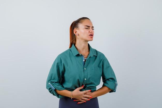 Jovem senhora que sofre de dor de estômago, está vestindo uma camisa verde e parece dolorida. vista frontal.