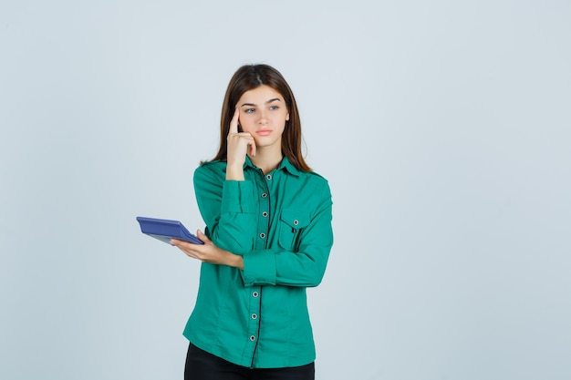 Jovem senhora segurando a calculadora enquanto segura o dedo nas têmporas de camisa verde e olhando pensativa, vista frontal.