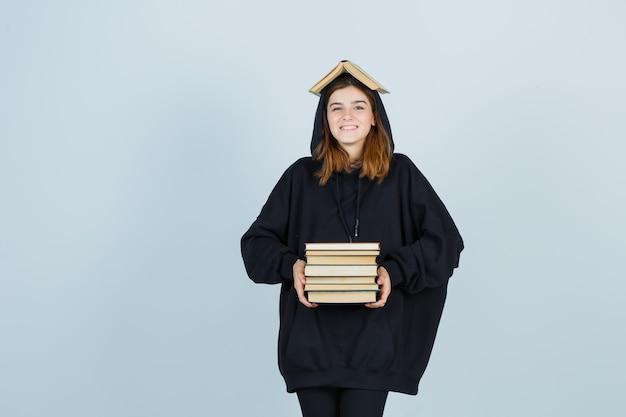 Jovem senhora segurando o livro acima da cabeça como telhado, segurando livros na frente dela em um moletom com capuz enorme, calças e uma aparência engraçada. vista frontal.