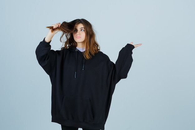 Jovem senhora segurando uma mecha de cabelo em um moletom com capuz grande, calças e olhando pensativa, vista frontal.