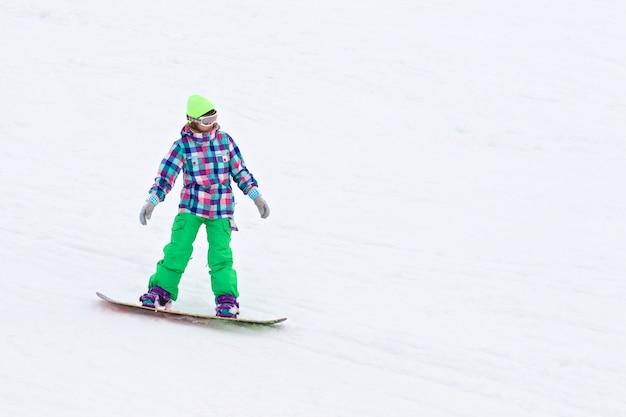Jovem senhora snowboarder descendo a colina