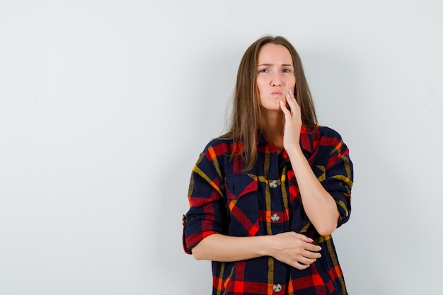 Jovem senhora sofrendo de dor de dente na camisa casual e parecendo desconfortável, vista frontal.