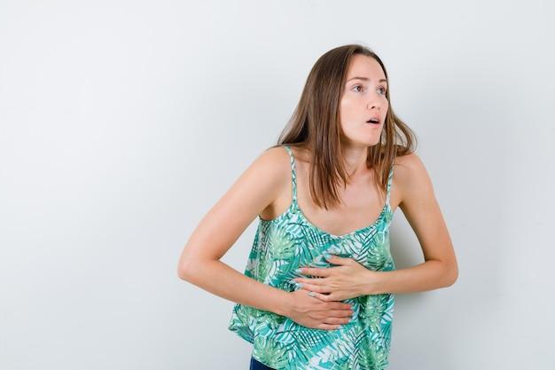 Jovem senhora sofrendo de dor de estômago e parecendo indisposta, vista frontal.