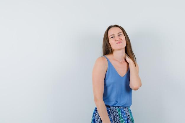 Jovem senhora sofrendo de dor no pescoço na camiseta, saia e parecendo irritada, vista frontal.