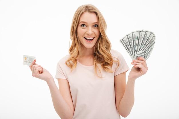 Jovem senhora sorridente segurando o dinheiro e cartão de crédito.