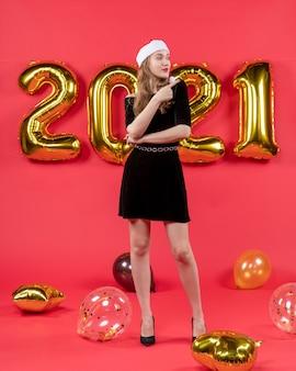 Jovem senhora vestida de preto apontando para algo em um balão vermelho