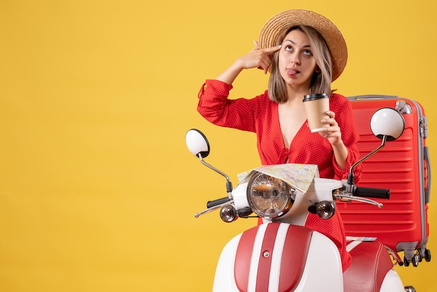 Jovem senhora vestida de vermelho com a língua para fora segurando a xícara de café perto de um ciclomotor