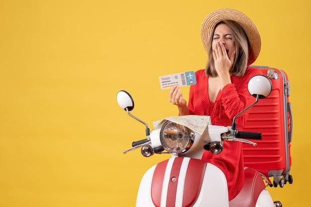 Jovem senhora vestida de vermelho segurando o tíquete, bocejando na motocicleta