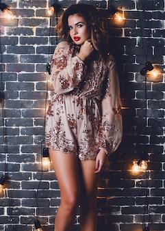 Jovem sensual e glamourosa posando em uma parede de tijolo urbana com decoração de iluminação