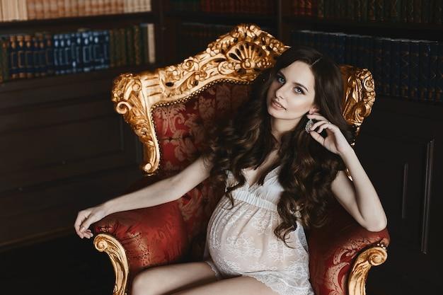 Jovem sensual e linda morena grávida com maquiagem macia em cueca de renda branca, sentada na poltrona vermelha vintage e posando no interior luxuoso