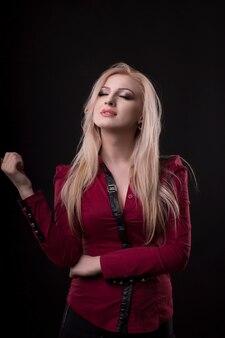 Jovem sensual vestida com blusa vermelha posando no estúdio