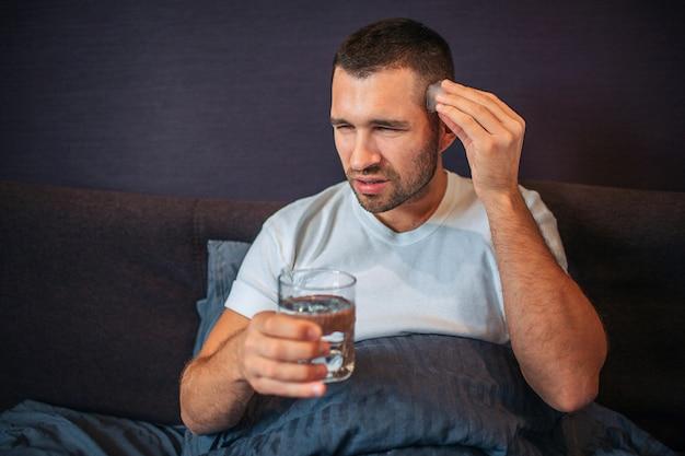 Jovem senta-se na cama e encolhe. ele tem dor de cabeça. cara mantém uma mão perto da cabeça e segura um copo de água com a outra. ele está coberto com um cobertor.
