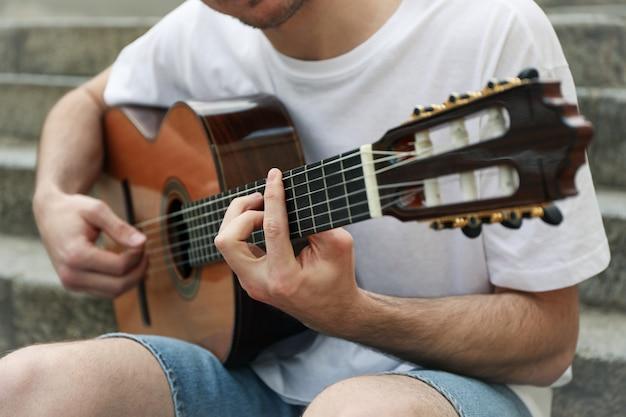Jovem senta-se nos degraus e tocar guitarra