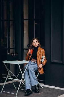 Jovem sentada do lado de fora do café tomando café