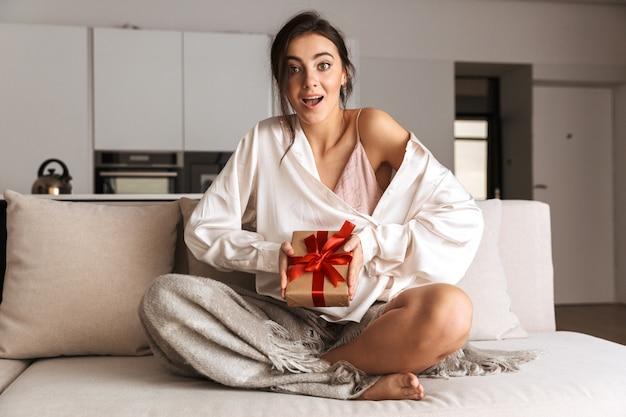 Jovem sentada em um sofá em casa, segurando uma caixa de presente