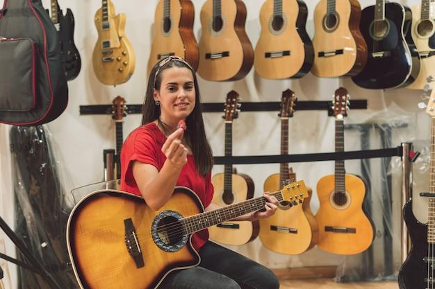 Jovem sentada em uma loja de guitarras cercada por guitarras espanholas prontas para tocar