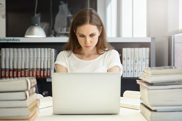 Jovem sentada na biblioteca com um laptop
