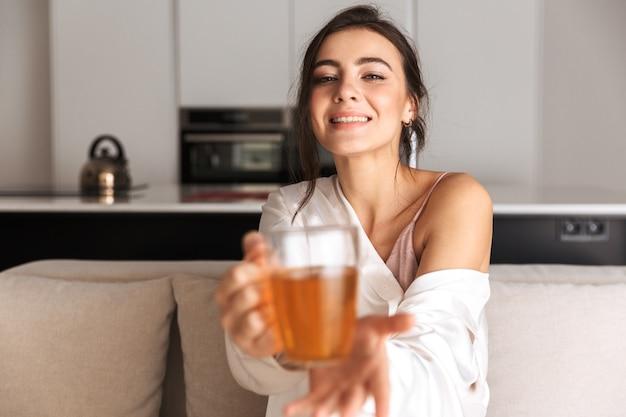 Jovem sentada na cozinha, segurando um copo com chá