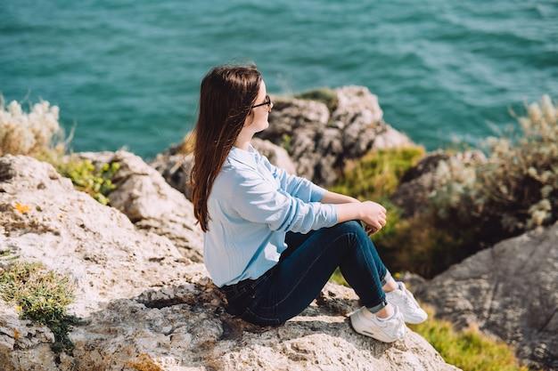 Jovem sentada nas pedras perto do mar.