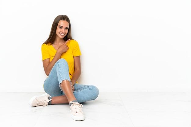 Jovem sentada no chão apontando para o lado para apresentar um produto