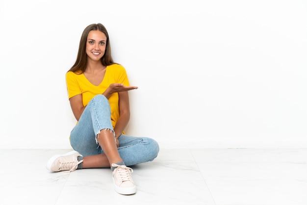 Jovem sentada no chão apresentando uma ideia enquanto olha sorrindo para