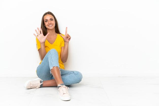 Jovem sentada no chão contando sete com os dedos
