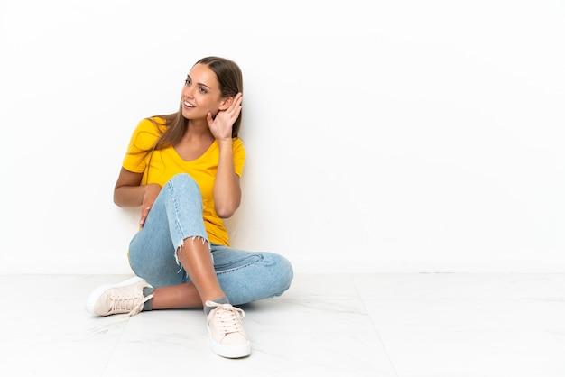 Jovem sentada no chão ouvindo algo colocando a mão na orelha