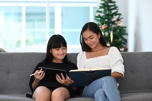 Jovem sentada no sofá e usando o tablet digital, fazendo lição de casa online durante as aulas extracurriculares com a mãe.