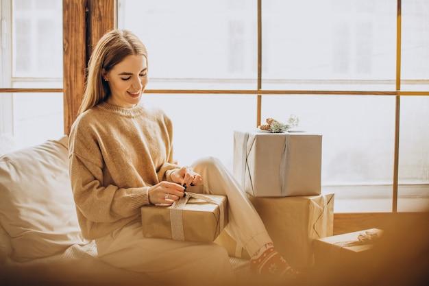 Jovem sentada perto da janela com presentes de natal