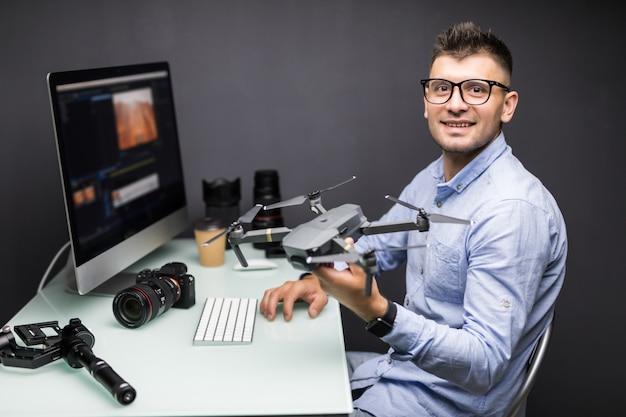Jovem sentado à mesa com diferentes dispositivos e gadgets segurando o drone nas mãos no escritório. jovem designer criativo olhando para longe em um escritório particular