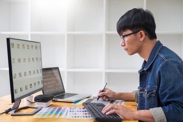 Jovem sentado à mesa e trabalhando juntos de designers criativos, trabalhando no estúdio fazendo alguns retoques em um projeto criativo.