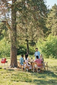 Jovem sentado ao lado da mesa servido na frente de seus amigos durante um jantar ao ar livre sob um pinheiro e pronunciando um brinde no fim de semana de verão