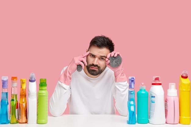 Jovem sentado ao lado de produtos de limpeza