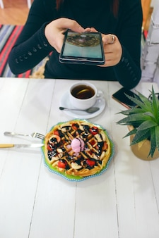 Jovem sentado caffe tomando café da manhã waffle com calda de chocolate, fatias de banana e morangos no prato de cerâmico verde e fotografou seu café da manhã