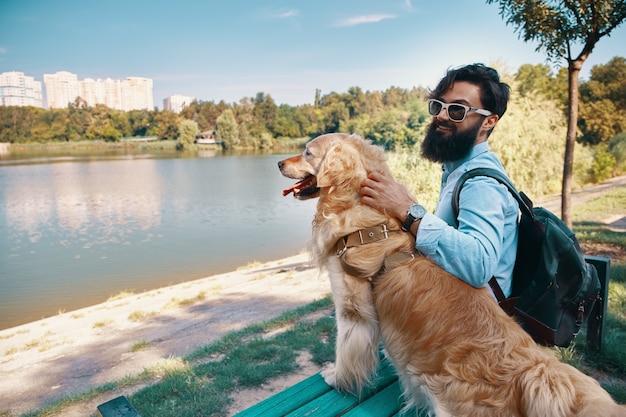 Jovem sentado com seu cachorro na cadeira no parque